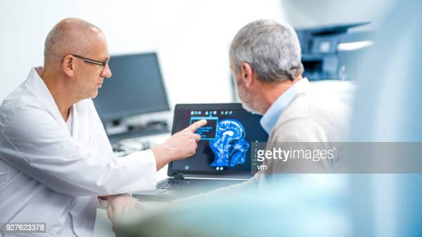 doctor showing patient his brainscan - hospital machine stock photos and pictures