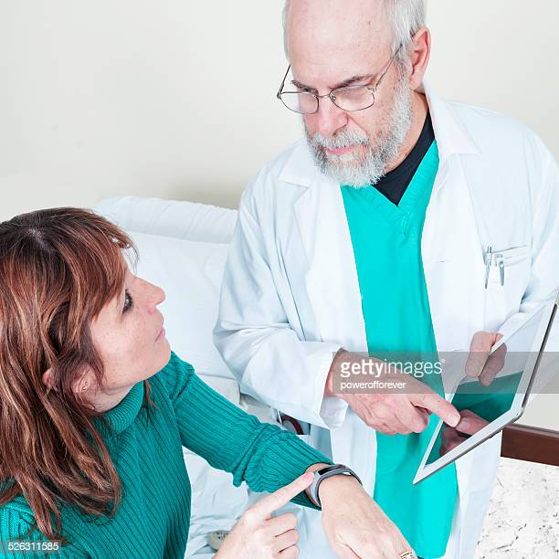 Doctor Showing Patient Smart Device to Monitor Her Health