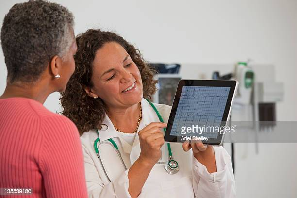 doctor showing patient test results on digital tablet - cardiologist stock pictures, royalty-free photos & images
