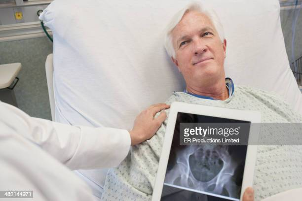 Doctor showing patient x-rays on digital tablet