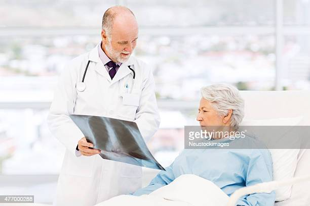 Doctor Showing X-Ray To Patient In Hospital