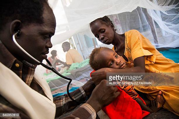 Doctor Simon Angelo examines Iman Steven suffering from tuberculosis held by her mother at the hospital of Doctors Without Borders on June 15 at the...