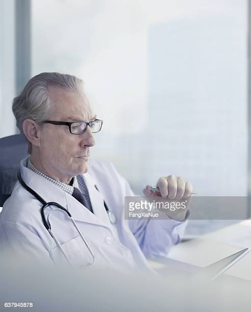 Doctor sitting and thinking alone in medical office