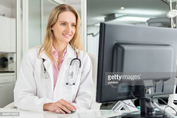 Doctor sitting at desk & using computer