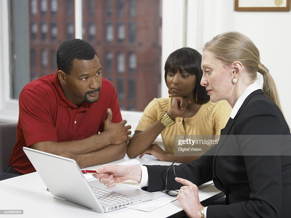 Doctor Sitting at Her Desk in a Clinic and Pointing to Her Laptop : Stock Photo