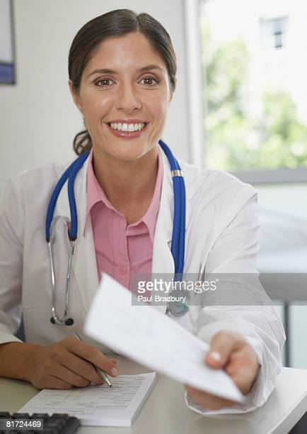 doctor sitting in office with paperwork smiling - one mid adult woman only stock pictures, royalty-free photos & images