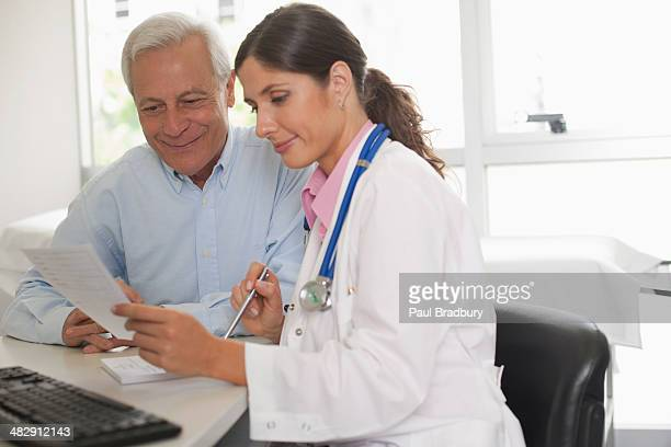 Doctor sitting in office with patient talking and holding paper