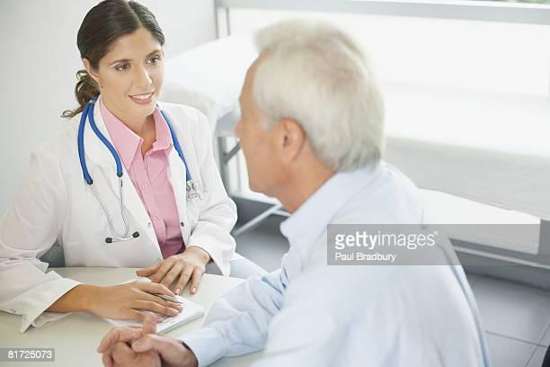 Arzt Sitzen im Büro mit Patienten reden und Lächeln