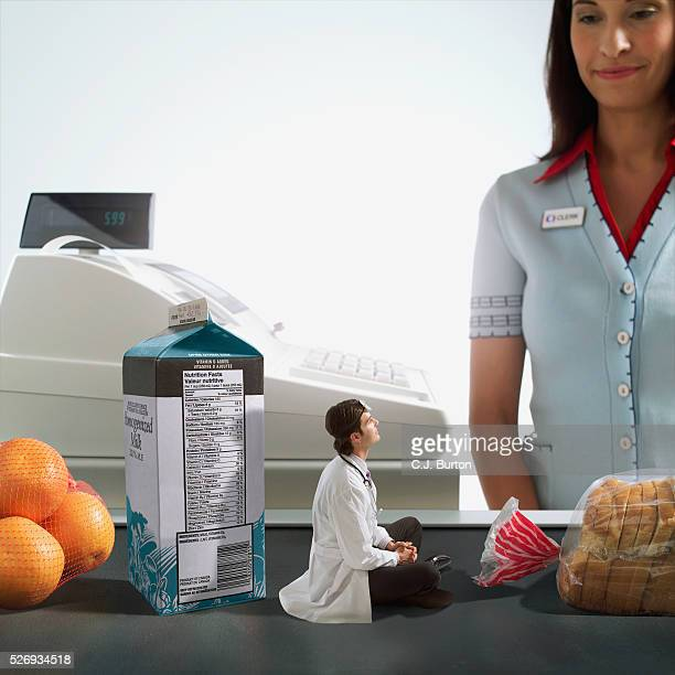 Doctor sitting on grocery store conveyor belt