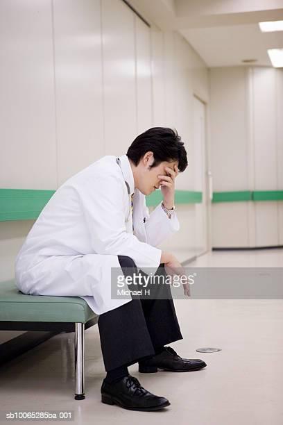 Doctor sitting with head in hands in hospital corridor
