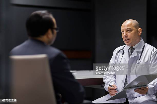 Doctor sitting with patient in meeting room