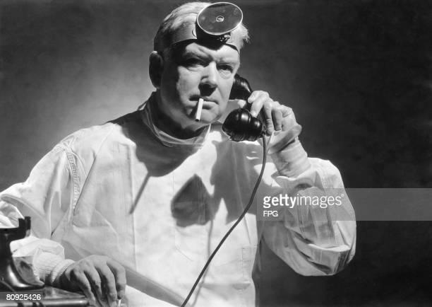 A doctor smoking a cigarette while taking a phone call circa 1950