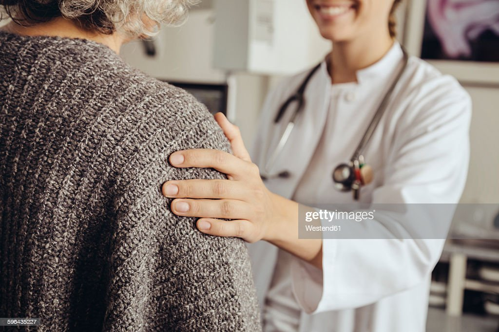 Doctor soothing senior patient : Stock-Foto