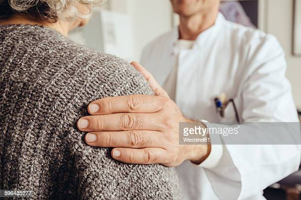 doctor soothing senior patient - hand on shoulder stock pictures, royalty-free photos & images