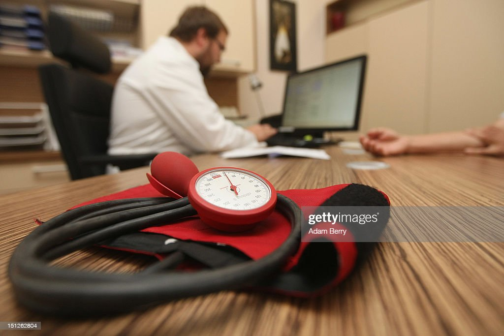 A doctor speaks to a patient as a sphygmomanometer, or blood pressure meter, lies on his desk on September 5, 2012 in Berlin, Germany. Doctors in the country are demanding higher payments from health insurance companies (Krankenkassen). Over 20 doctors' associations are expected to hold a vote this week over possible strikes and temporary closings of their practices if assurances that a requested additional annual increase of 3.5 billion euros (4,390,475,550 USD) in payments are not provided. The Kassenaerztlichen Bundesvereinigung (KBV), the National Association of Statutory Health Insurance Physicians, unexpectedly broke off talks with the health insurance companies on Monday.