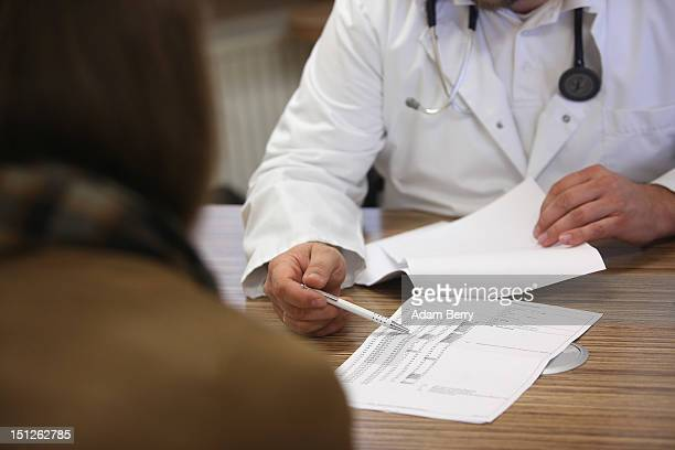 A doctor speaks with a patient about her high blood pressure or hypertension on September 5 2012 in Berlin Germany Doctors in the country are...