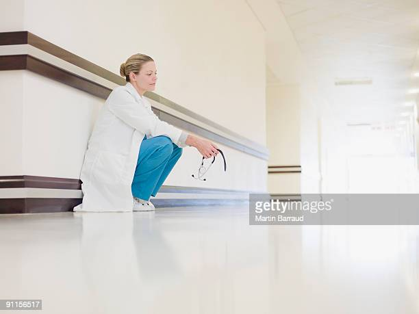 Doctor squatting in hospital corridor