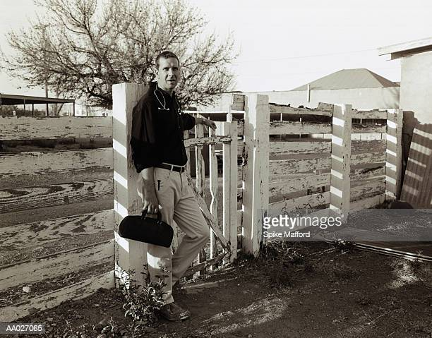 Doctor Standing by a Fence