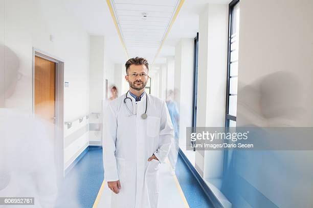 doctor standing in corridor of medical clinic - mani in tasca foto e immagini stock