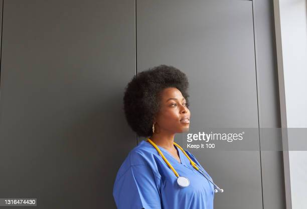 doctor standing, looking contemplative through a window at work. - african ethnicity stock pictures, royalty-free photos & images