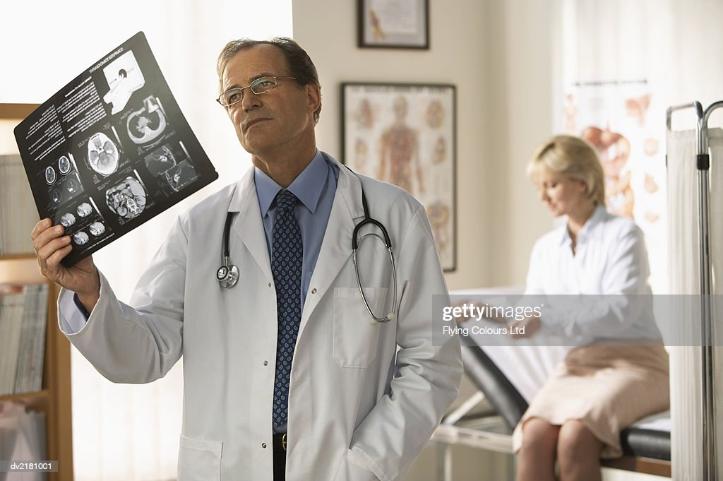 Doctor Stands in His Surgery, Examining an X-Ray : Stock Photo