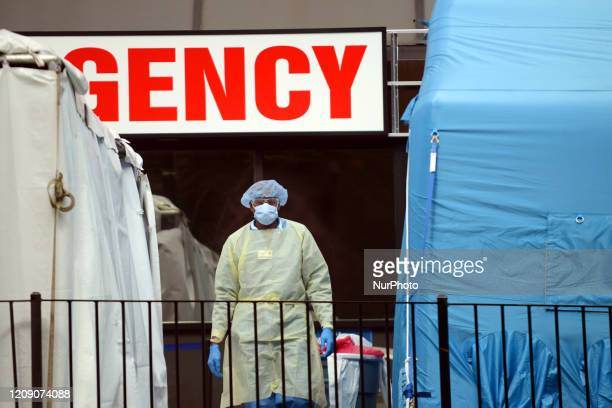 A doctor stands in the middle of the makeshift COVID19 screening center outside Elmhurst Hospital in Queens New York Thursday April 2nd 2020