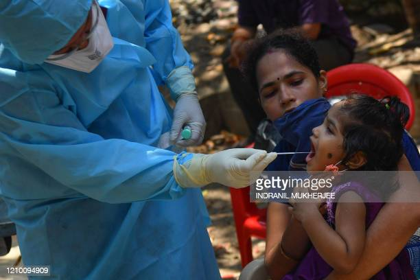 A doctor takes a swab sample of a resident at a COVID19 coronavirus testing drive inside the Dharavi slums during a governmentimposed nationwide...