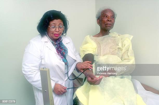 Doctor takes an elderly man's blood pressure March 13, 1994 at the Sydenham Health Center in Harlem, NewYork.