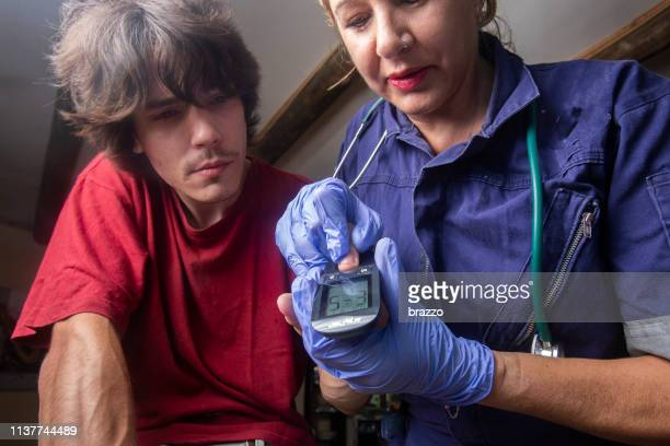 doctor takes blood sugar reading on a patient's finger - film and television screening stock pictures, royalty-free photos & images