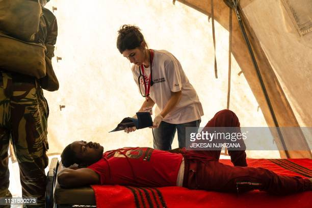 A doctor takes care of a young man in a temporary treatment camp after he was rescued and airlifted by helicopter in Chimanimani on March 20...