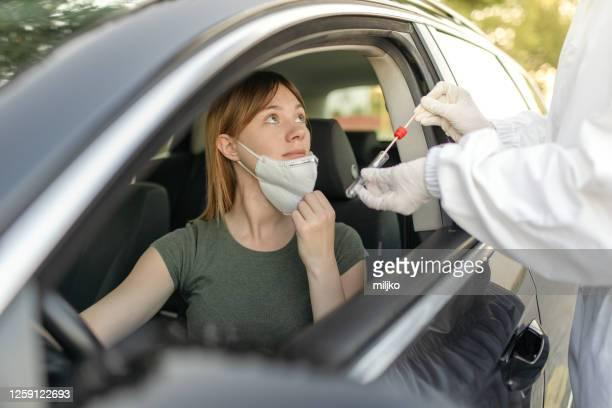 a doctor taking a swab from a car driver in front of public building - medical test stock pictures, royalty-free photos & images