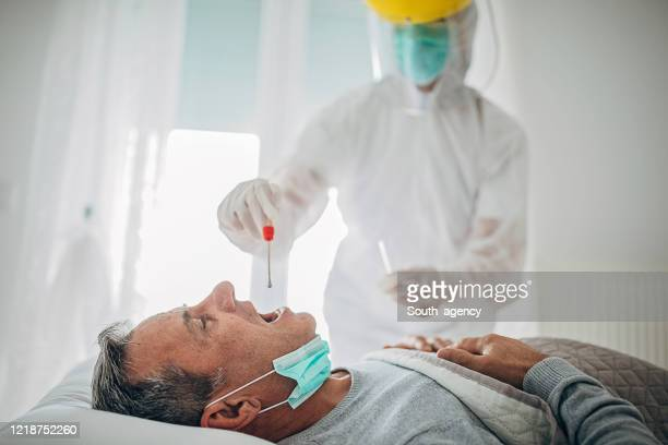 doctor taking a throat swab test from a senior man at home for covid-19 testing - helmet visor stock pictures, royalty-free photos & images