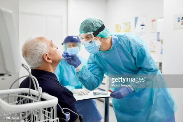 arzt, der coronavirus-probe aus der nase des männlichen patienten nimmt - wissenschaftliches experiment stock-fotos und bilder