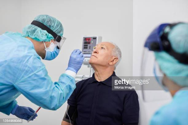 doctor taking coronavirus sample from male's nose, pcr. - scientific experiment stock pictures, royalty-free photos & images