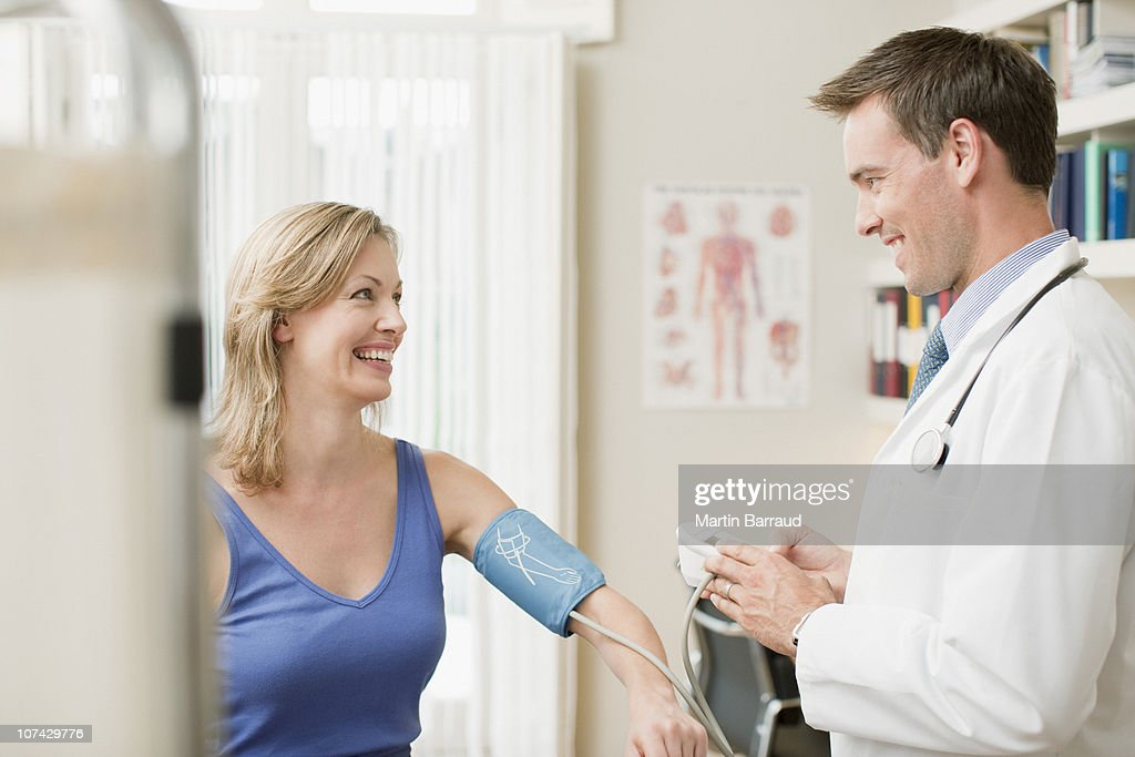 Doctor taking patients blood pressure in doctors office : Stock Photo