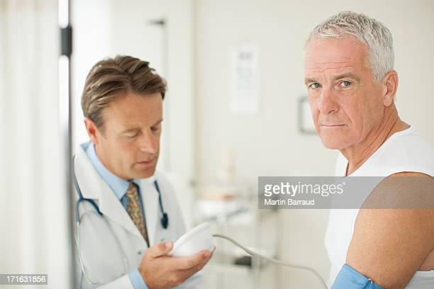 Arzt mit Patienten mit den Blutdruck im Doctor's office