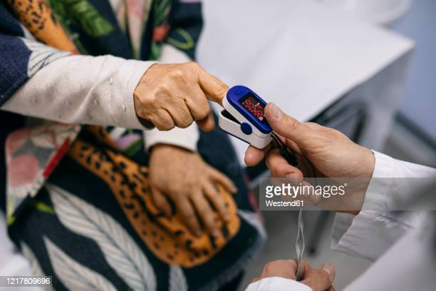 doctor taking patient's pulse in medical practice - pulse oximeter stock pictures, royalty-free photos & images