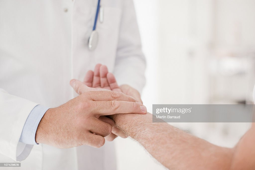 Doctor taking patients pulse : Stock Photo