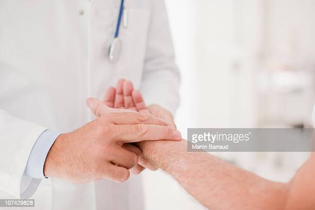 Doctor taking patients pulse