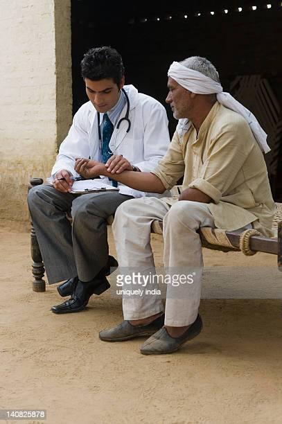 Doctor taking pulse of a farmer, Hasanpur, Haryana, India