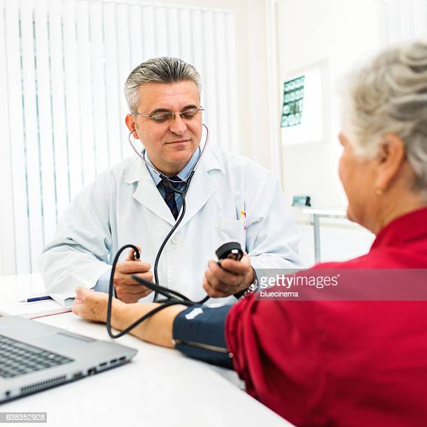 Doctor taking senior woman blood pressure