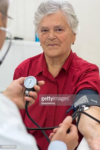 Doctor taking senior woman blood pressure