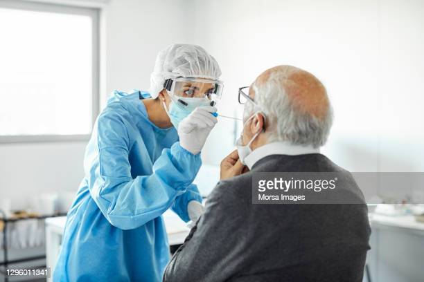 doctor taking swab test sample of elderly patient, pcr. - medical examination stock pictures, royalty-free photos & images