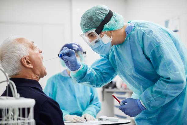 醫生從男性患者,PCR進行咽喉拭子測試