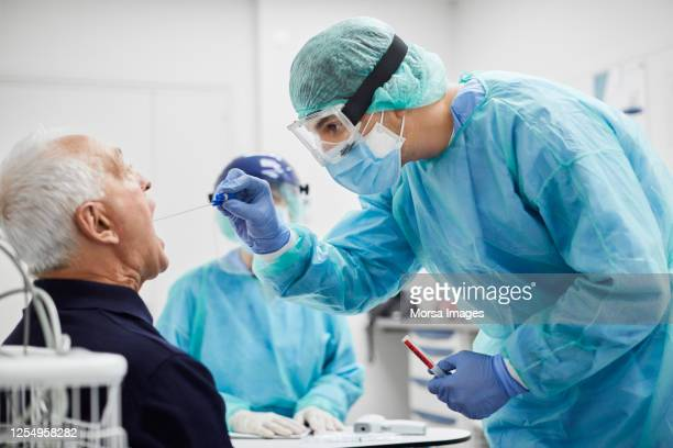 doctor taking throat swab test from male patient, pcr - corona virus stock pictures, royalty-free photos & images