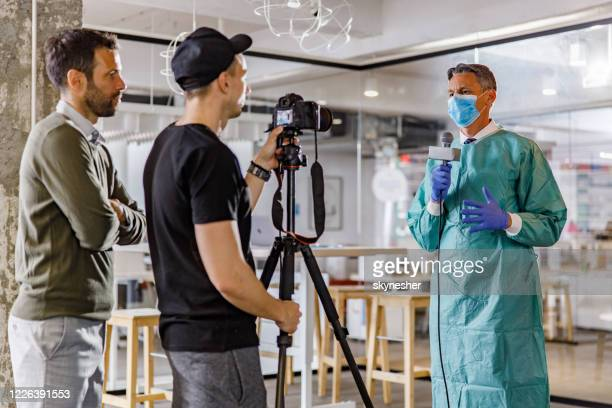 doctor talking on a microphone about current epidemic during tv interview in hospital. - journalist stock pictures, royalty-free photos & images