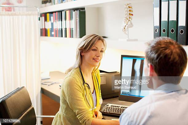 doctor talking over x-ray with patient in doctors office - medical x ray stock pictures, royalty-free photos & images