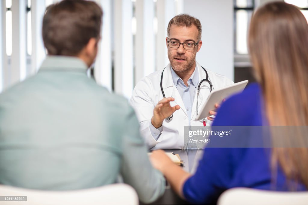 Doctor talking to couple in medical practice : Stock Photo