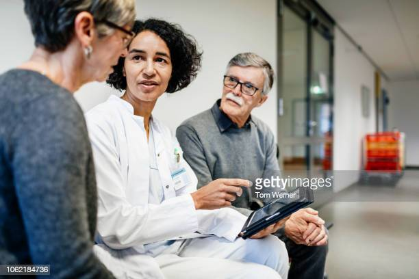 doctor talking to elderly couple about test results - outpatient care stock pictures, royalty-free photos & images