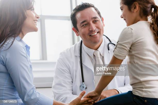 Doctor talking to girl and her mother in examination room